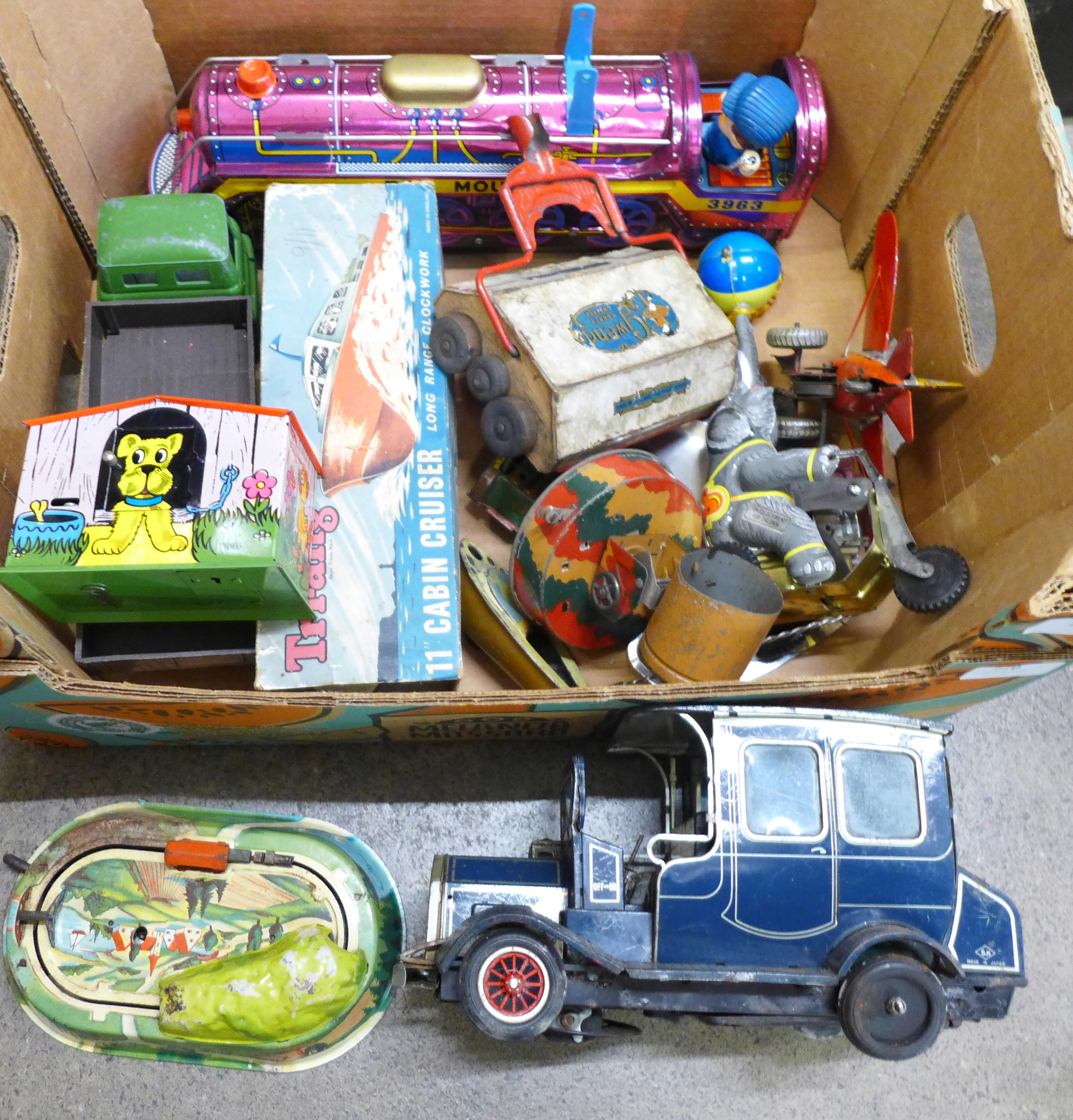 A collection of tin-plate toys, Tri-ang cabin cruiser, locomotive, etc.