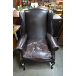 A chestnut brown leather wingback armchair