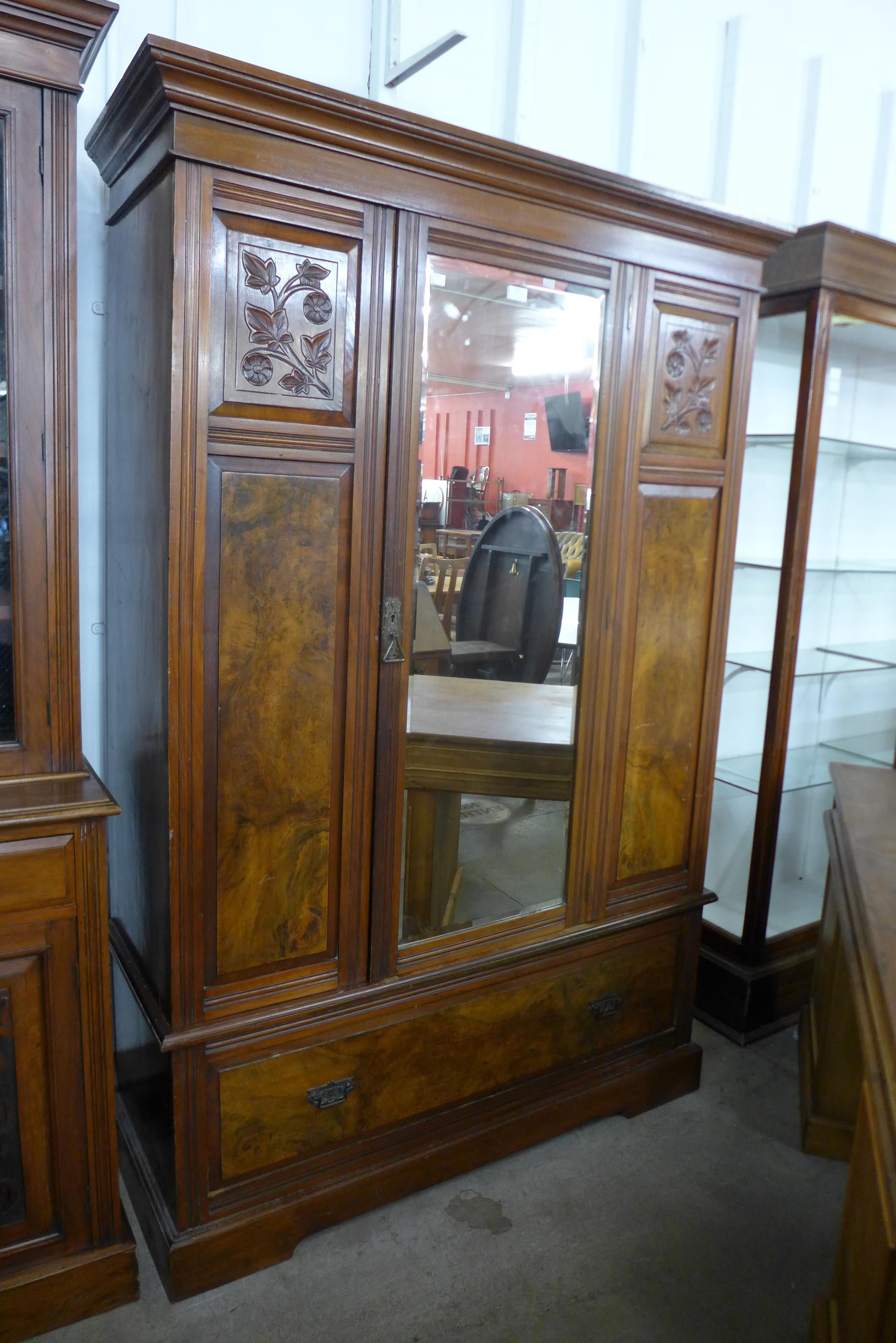 A Victorian carved walnut and burr walnut wardrobe