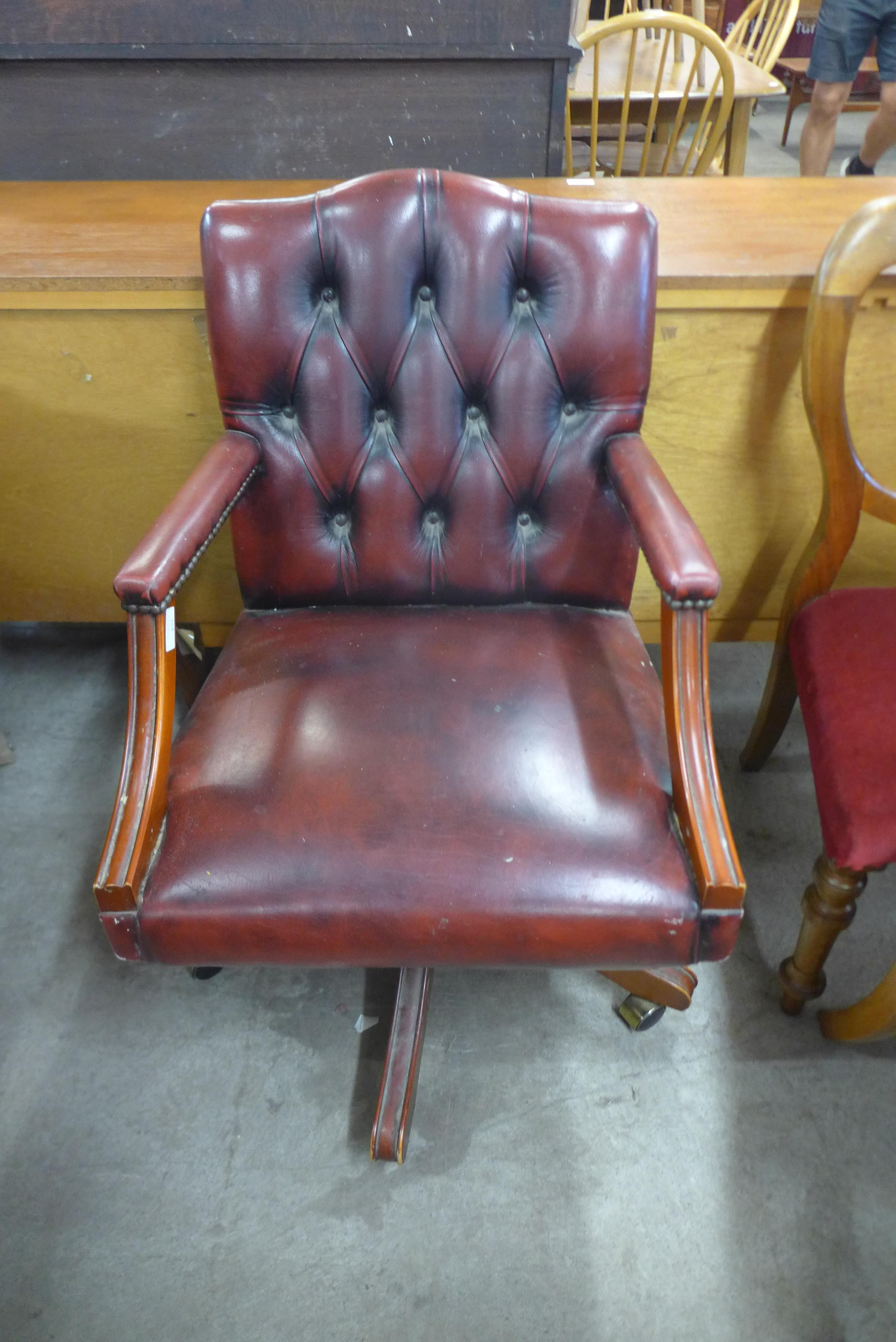 A red leather buttoned revolving desk chair
