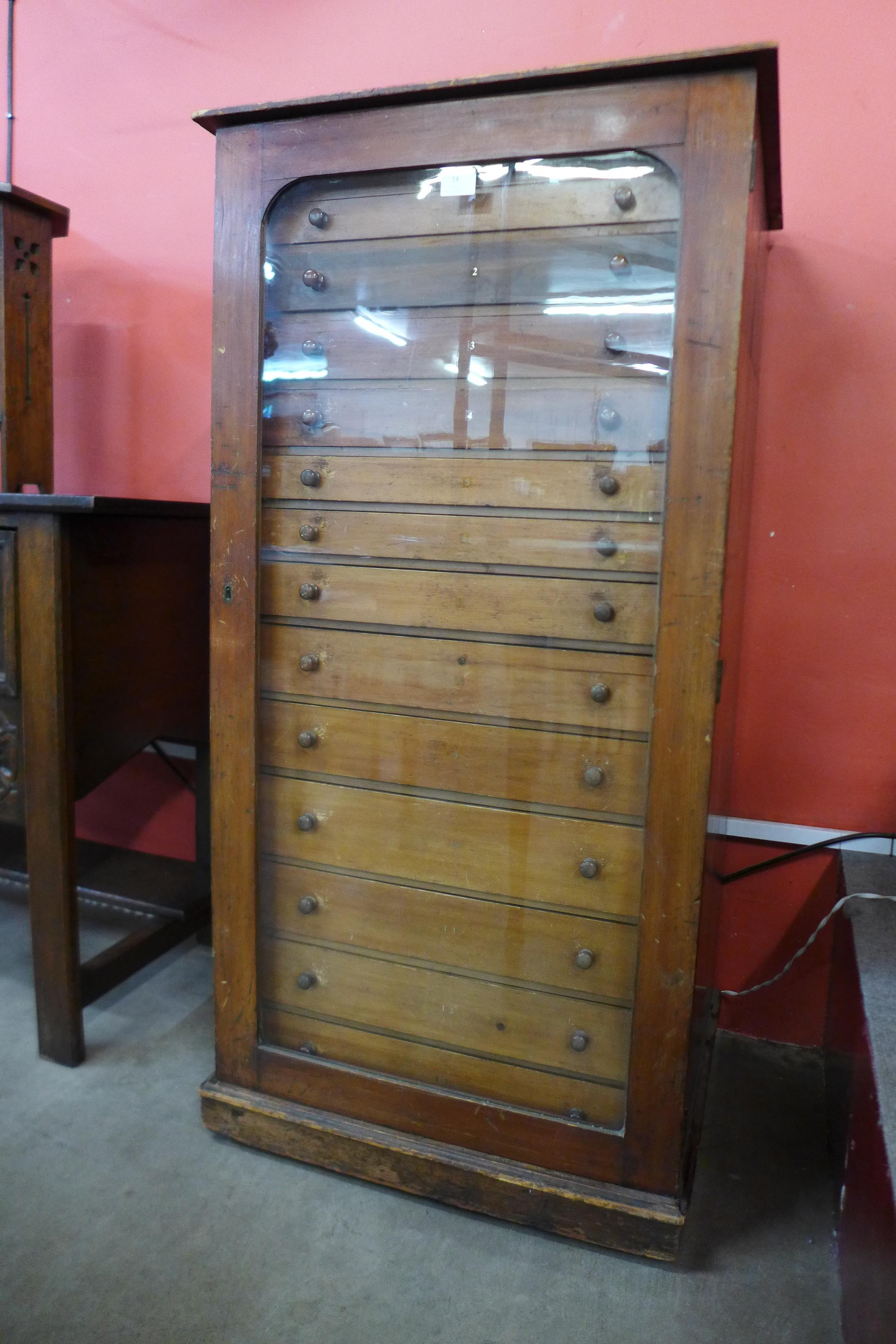 A Victorian mahogany museum collectors cabinet, with single glazed door revealing thirteen drawers