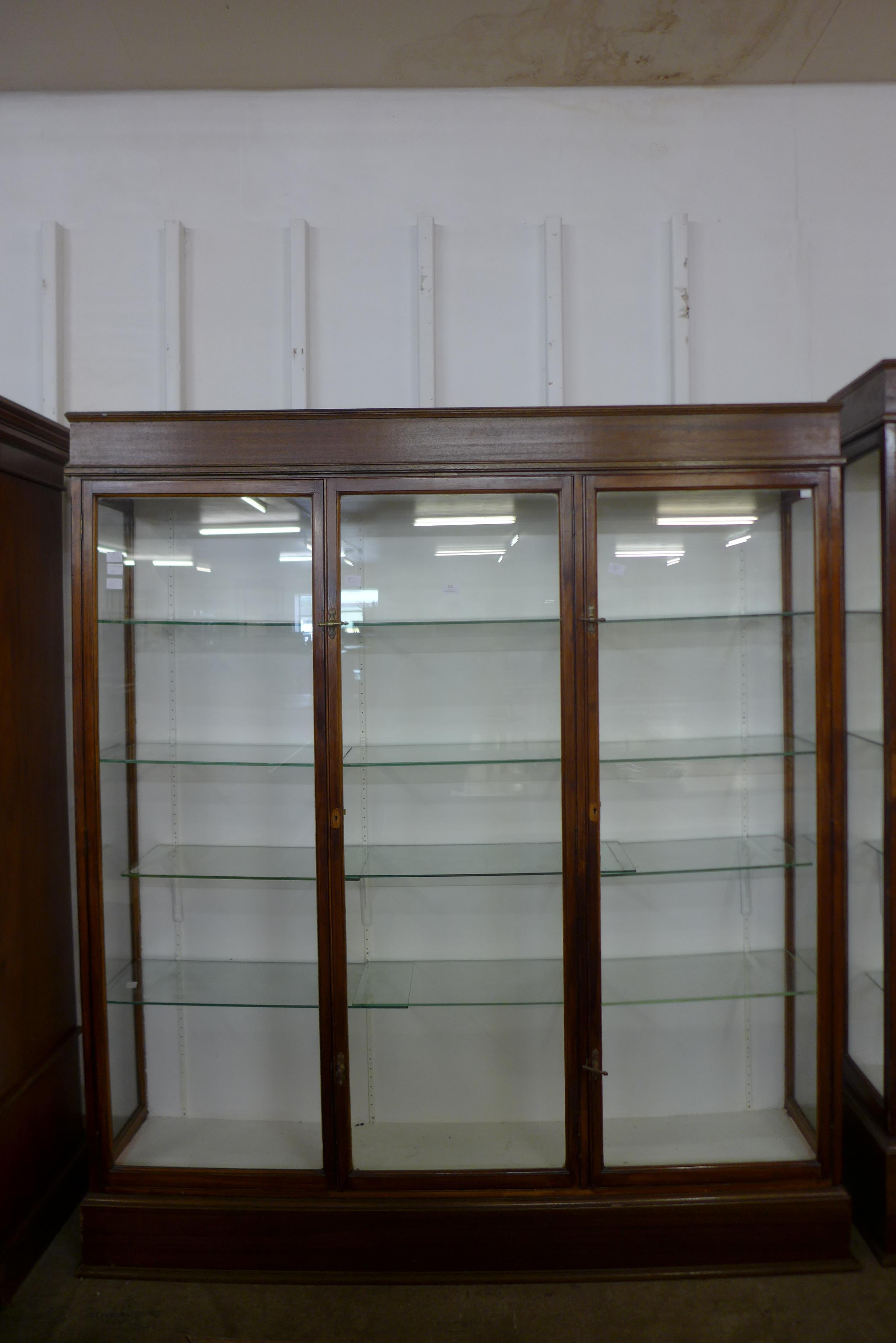 A large mahogany three door shop display cabinet, made by F. Maund & E. Berg Ltd., Showcases &