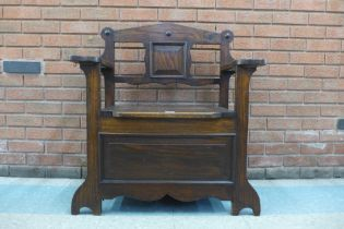 An Arts and Crafts oak hall seat