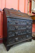 A Victorian Jacobean Revival carved oak bureau