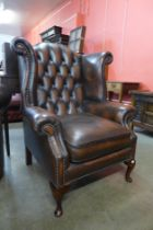 A mahogany and brown leather wingback armchair