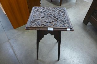 An Arts and Crafts carved oak occasional table