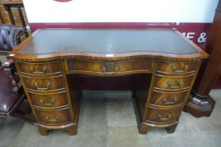 A mahogany and green leather topped serpentine desk