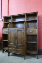 An Arts and Crafts oak open breakfront bookcase