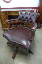 A mahogany and burgundy leather revolving desk chair