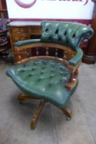 A mahogany and green leather revolving desk chair