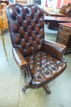 A mahogany and buttoned chestnut brown revolving desk chair