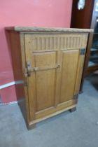 A Cotswold School oak single door side cabinet