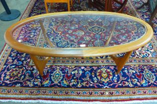 A Stonehill Stateroom teak and glass topped oval coffee table