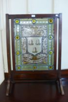 An Arts and Crafts mahogany and leaded glass armorial fire screen, painted with Whalley Family,