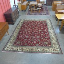 A Persian hand made red ground rug, 335 x 250cms