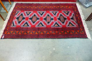 A Persian hand made red ground rug, 204 x 125cms