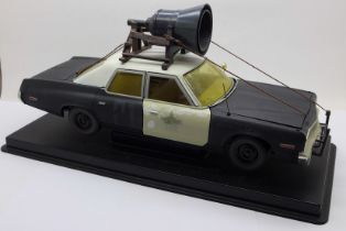 A heavy die-cast model Blues Brothers police car on a plinth, 31cm