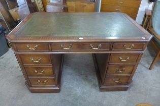 A Victorian style mahogany and green leather topped partners desk