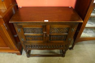 A 17th Century style carved oak two door cupboard