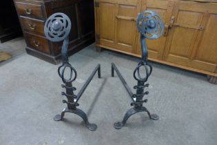A pair of Arts and Crafts cast steel andirons