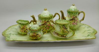 A Lymes China miniature tea service with tray, decorated in the Victorian Birds design