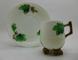 A Minton cup and saucer with relief detail, a/f, hairline crack in cup