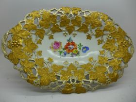A Meissen hand painted oval pierced dish, floral decoration to the centre, vine leaves in gold