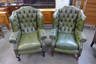 A pair of mahogany and green buttoned leather wingback armchair