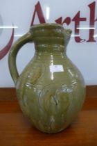 A large celadon glazed terracotta jug