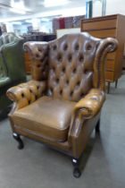A mahogany and tan buttoned leather wingback armchair