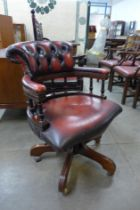 A mahogany and red leather captain's revolving desk chair