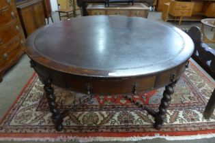 An early 20th Century oak and leather topped drum shaped library table
