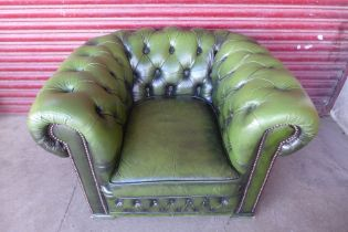 A green buttoned leather club chair