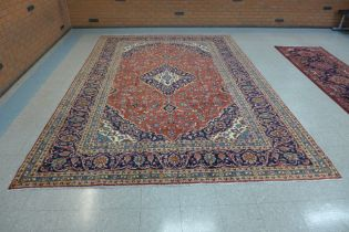 A large Persian red ground Kashan rug, 410 x 283cms