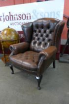 A chestnut mahogany and brown buttoned leather wingback armchair