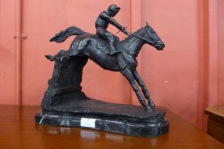 A bronze figure of a race horse and jockey, on black marble plinth