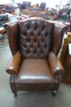 A mahogany and chestnut brown leather wingback armchair