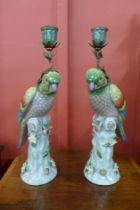 A pair of French style porcelain parrot candlestick holders