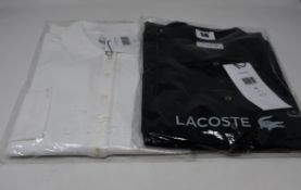 Two as new Lacoste polo shirts; black (Size 46) and white (Size 36).