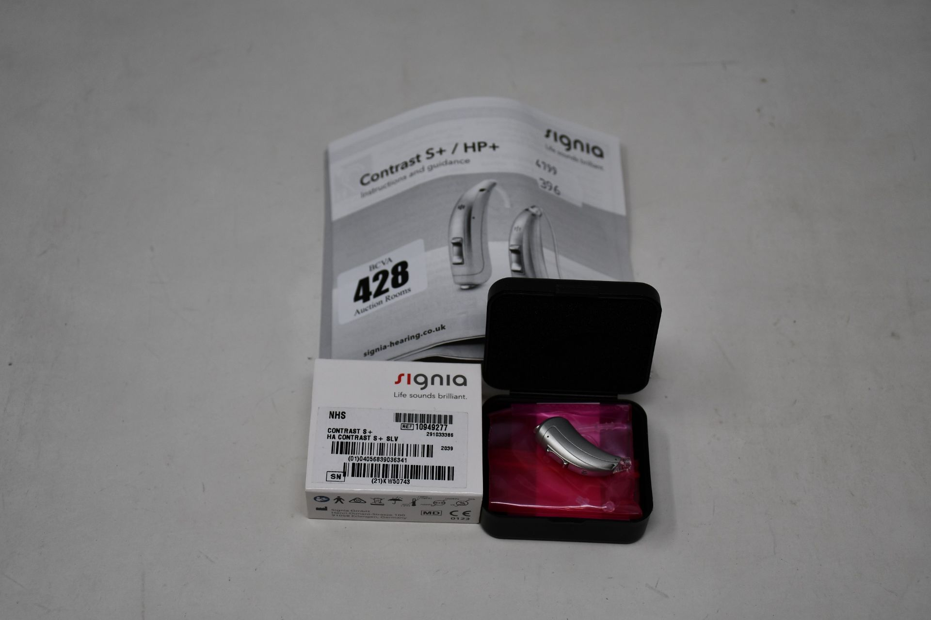 A boxed as new Signia Contrast S+ hearing aid in silver.