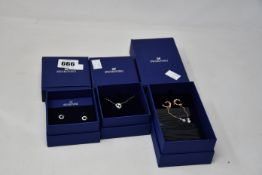 Three boxed as new Swarovski jewellery items to include one attract pierced earrings white and