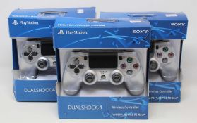 Four boxed as new Sony PlayStation DUALSHOCK 4 Wireless Controllers in Silver (some damage to box).
