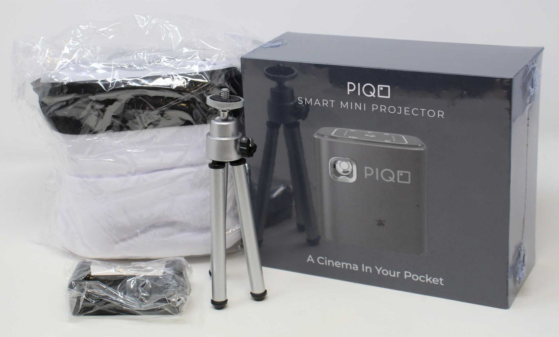 A boxed as new Piqo Smart Android Mini Projector (UK plug adaptor required) (Box sealed) with fabric