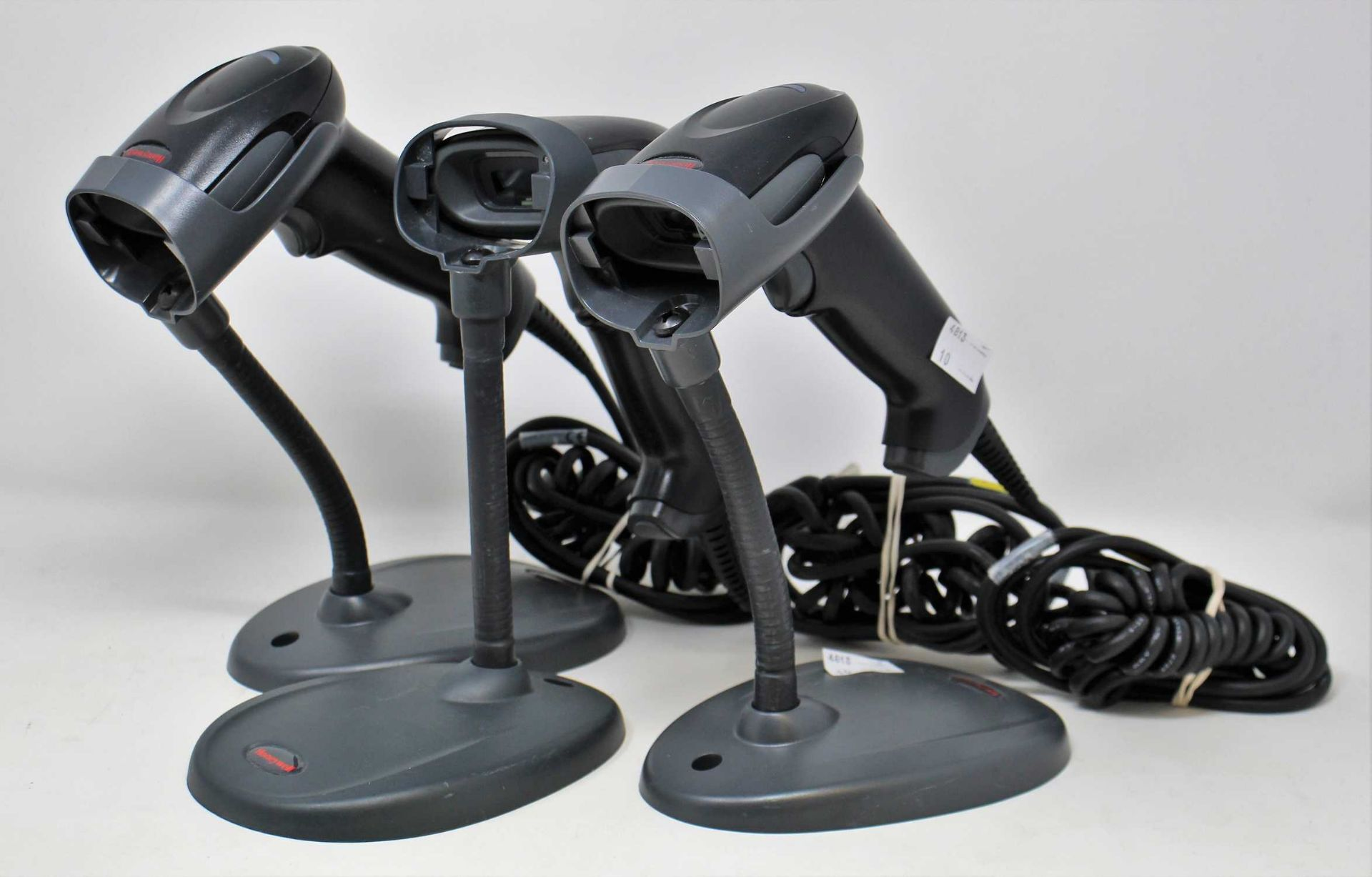 Three pre-owned Honeywell Voyager 1250g USB Barcode Scanners (P/N: 1250g-2) with stands.
