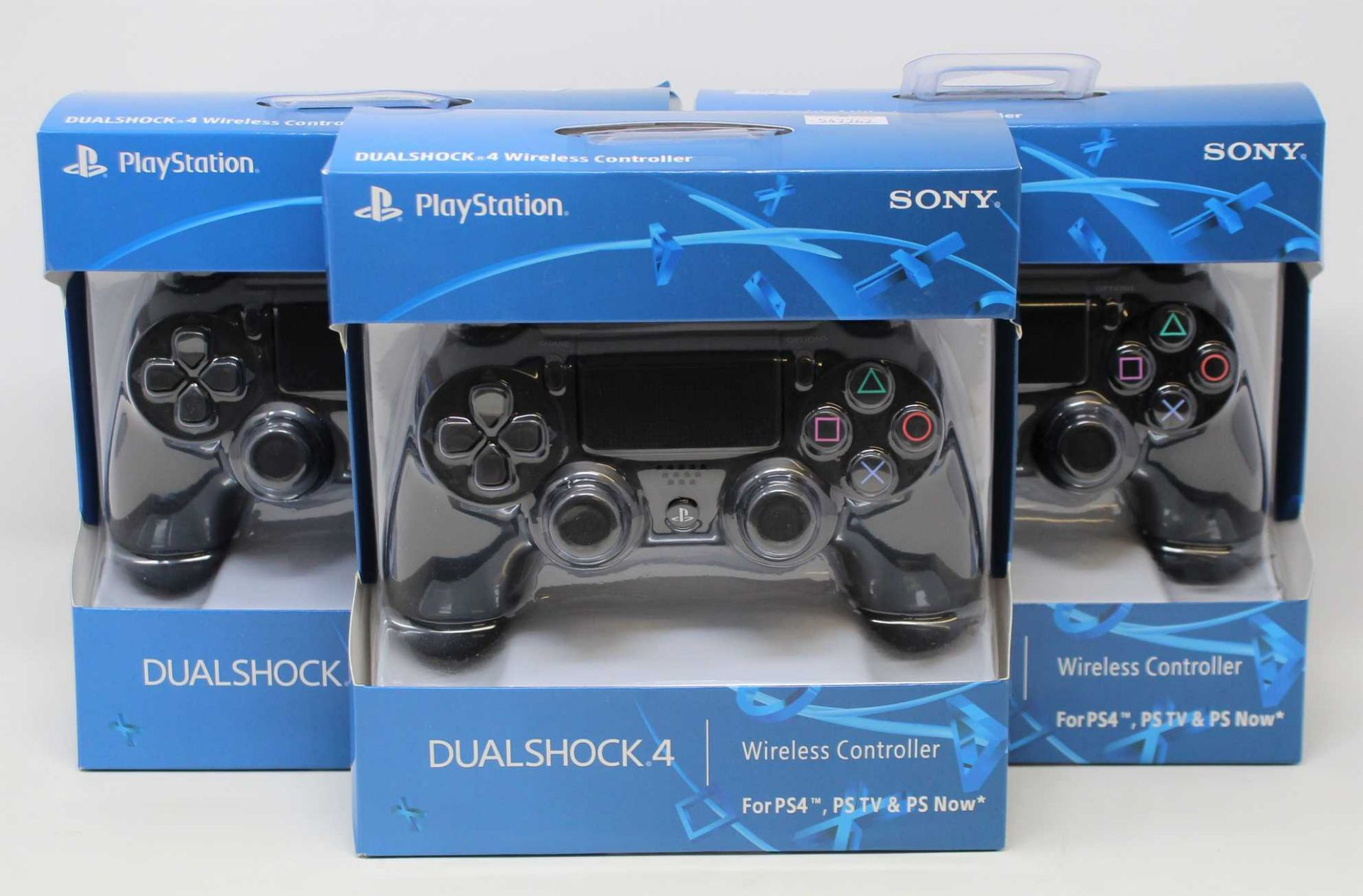 Four boxed as new Sony PlayStation DUALSHOCK 4 Wireless Controllers in Black (some damage to box).