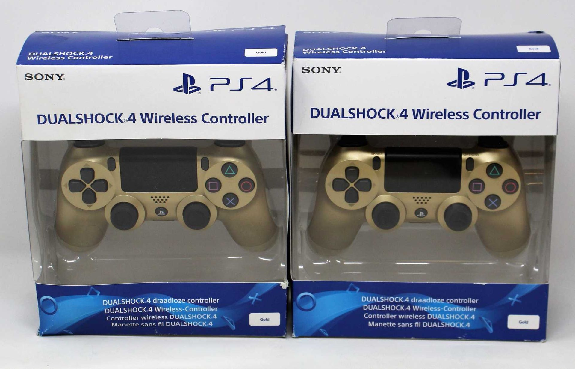 Two boxed as new Sony PlayStation DualShock 4 Wireless Controllers in Gold (Some damage to boxes).
