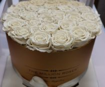 An as new The Million Roses LA gold premium box with white roses.