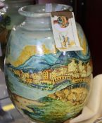 A handmade vase picturing an Italian landscape and a ceramic bauble from Ceramiche Laureanti.
