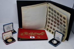 A box of World Collection coins to include some silver crowns, etc.