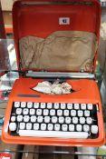 A pre owned Hermes Baby vintage typewriter in orange (Some slight damage to case).